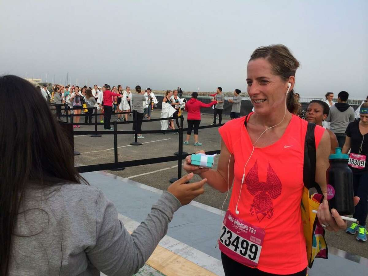 A runner is handed a Tiffany necklace after crossing the finish line of the 2014 Nike Women's Half Marathon in San Francisco, Sunday, October 19, 2014.
