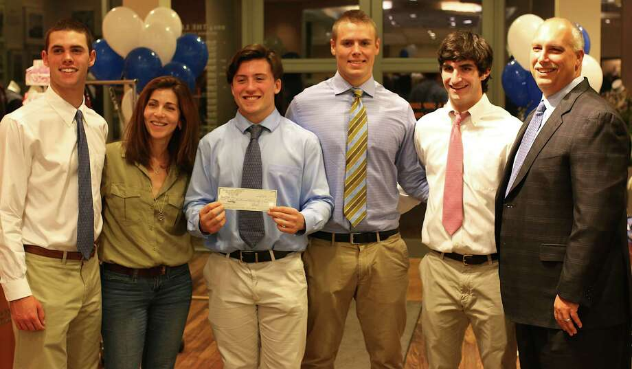 Staple's High Schopol football captains and their head coach presented the Westport-based nonprofit Pink Aid a check for $8,300, the proceeds of the team's Get Your Pink On fundraiser. From left are Teddy Coogan, Pink Aid board member Tammy Zelkowitz, Matty Jacowleff, Jackson Hoebermann, Jake Melnick, and coach Marce Petroccio. Westport CT. October 2014. Photo: Westport News/Contributed Photo / Westport News