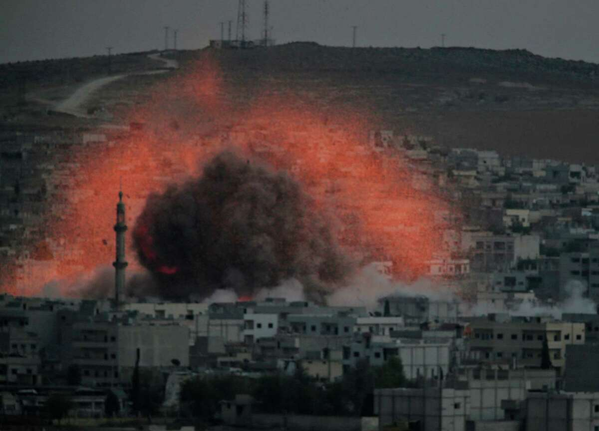 Thick smoke and debris rise from an airstrike by the US-led coalition, as light from the explosion is seen in Kobani, Syria while fighting continued between Syrian Kurds and the militants of Islamic State group, as seen from Mursitpinar on the outskirts of Suruc, at the Turkey-Syria border, Saturday, Oct. 18, 2014. Kobani, also known as Ayn Arab, and its surrounding areas, has been under assault by extremists of the Islamic State group since mid-September and is being defended by Kurdish fighters.Latest from AP: Turkey would oppose US arms transfers to Kurds