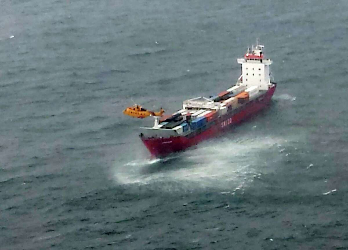 In this aerial photo provided by the Department of National Defense Maritime Forces Pacific, a Canadian Coast Guard helicopter flies near a Russian container ship, carrying hundreds of tons of fuel drifting without power in rough seas off British Columbia's northern coast on Friday, Oct. 17, 2014. The Canadian Forces' joint rescue coordination center in Victoria said the Russian carrier Simushir lost power late Thursday night off Haida Gwaii, also known as the Queen Charlotte Islands, as it was making its way from Washington state to Russia.AP story: Container ship towed away from Canadian coast