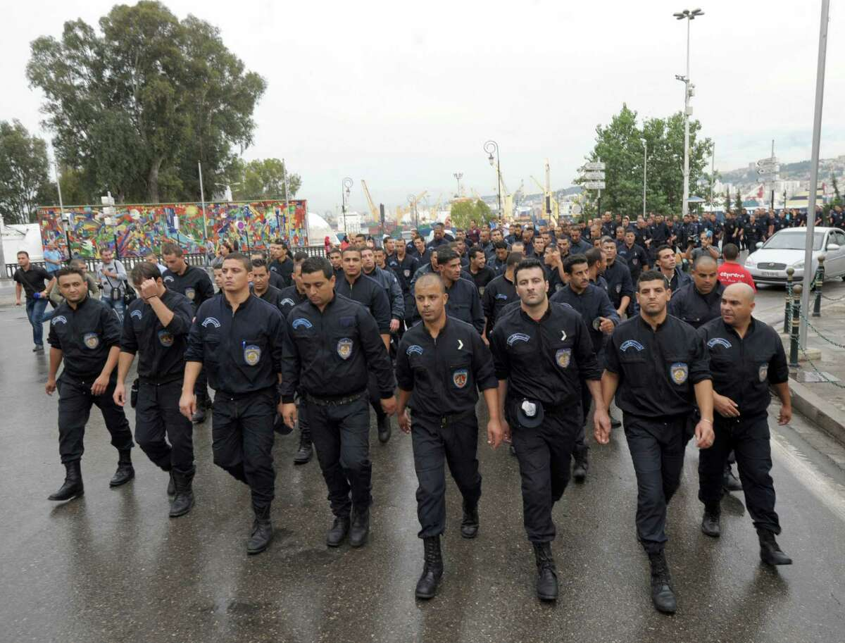Some 150 members of Algeria's police force stage an unprecedented march through the Algerian capital, Algiers, Tuesday, Oct. 13, 2014, in solidarity with their colleagues in the south. Wearing blue uniforms but without weapons or armor, the riot police marched silently along the highway from their barracks into Algiers, through the rain and to the seat of the government where they were briefly met by the local governor. The police said privately they were marching in solidarity with their embattled colleagues in Ghardaia who face daily attacks as they struggle to keep apart warring Berber and Arab communities.