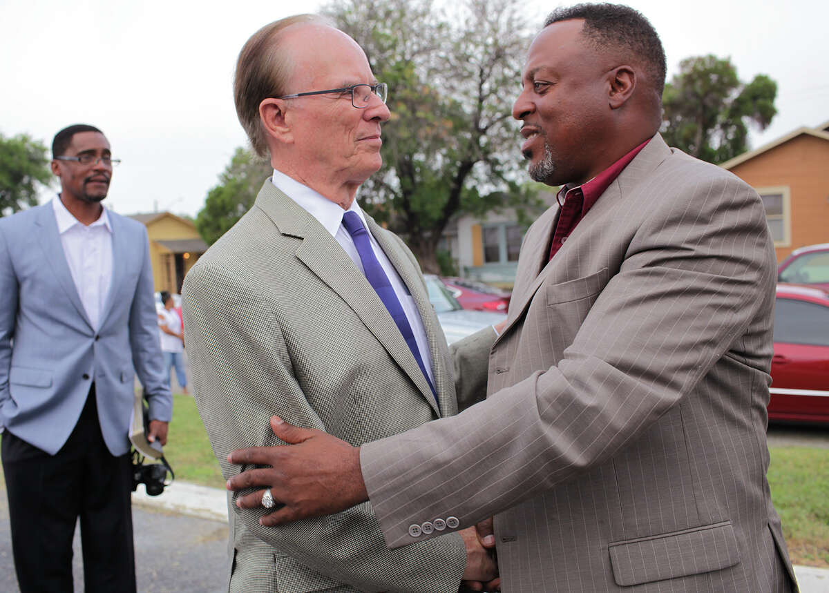 New Jerusalem Baptist Church Pastor Jeffery A. Garner, right, greets Bexar County Judge Nelson Wolff before a Healing Service, Sunday, Oct. 19, 2014. The service was held in the parking lot a week after the church building was destroyed in a fire on Monday.