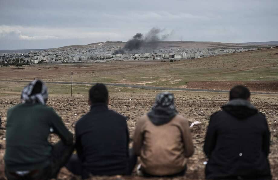 Kurds watch the Syrian town of Kobane, also known as Ain al-Arab, from the southeastern Turkish village of Mursitpinar. Islamic militants are battling for the Syrian town, which is just a few miles from Turkey. Photo: BULENT KILIC / AFP/Getty Images / AFP