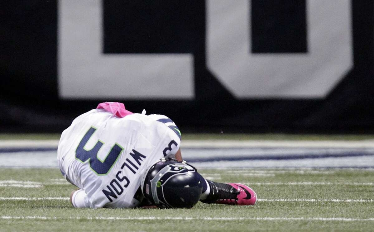Jim Moore says Seattle's weak offensive line will cost the Seahawks a post-season. This is bad news for Russell Wilson. Take a look at some of the harder hits Wilson has taken in recent years. (AP Photo/Tom Gannam)