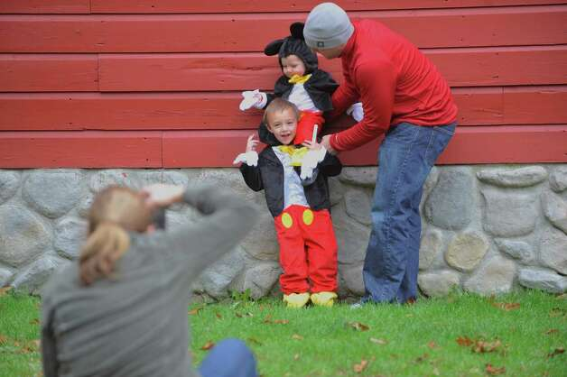 Bob Picard works to pose his two sons, Liam, 3, and Oliver, 1, as their mom, Amy, gets set to take their photo during the Fall Festival at the Pruyn House on Sunday, Oct. 19, 2014, in Latham, N.Y.  Both boys were dressed as Mickey Mouse.  Amy Picard said it will probably be the only time that her older son wanted to dress up to be what the younger one had chosen to be.  The annual event is hosted by the The Greater Loudonville Association.   (Paul Buckowski / Times Union) Photo: Paul Buckowski / 00029047A