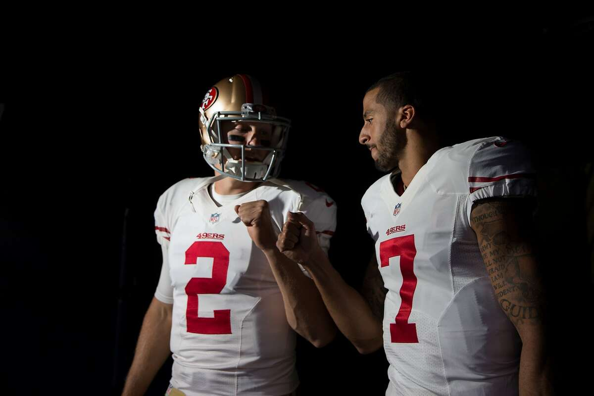 In thisOctober 19, 2014 file photo, quarterback Colin Kaepernick #7 and quarterback Blaine Gabbert #2 of the San Francisco 49ers bump fistsbefore emerging from the visiting tunnel before a game against the Denver Broncos at Sports Authority Field at Mile High on in Denver, Colorado.The Broncos have reportedly been working on restructuring Colin Kaepernick's contract.