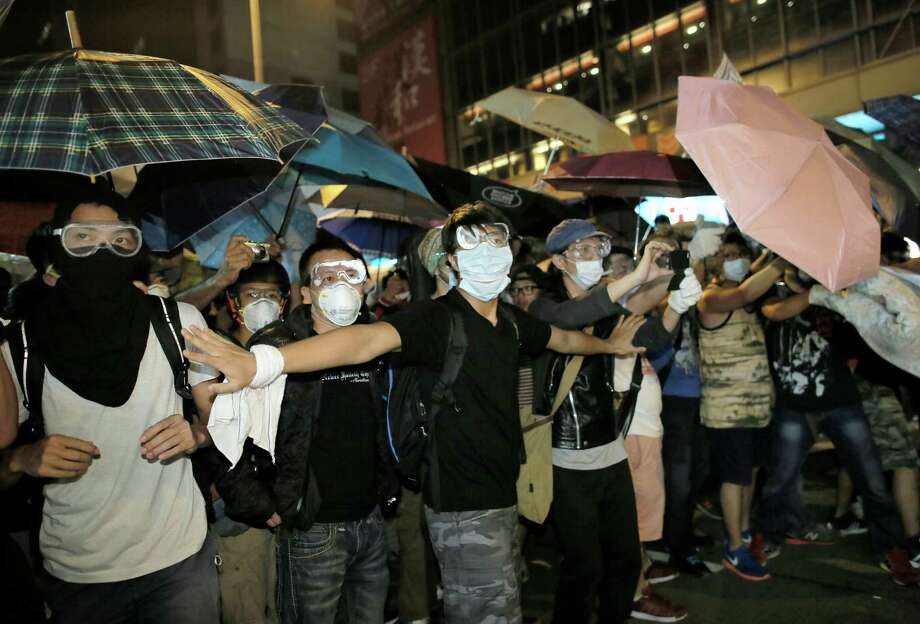 Pro-democracy protesters in the Mong Kok district of Hong Kong battled police Saturday and early Sunday. Police cleared most roadblocks, but an estimated 8,000 protesters retook the territory, a turnout fueled in part by Web platforms. Photo: Vincent Yu, STF / AP