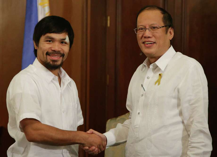 Filipino boxing hero and congressman Manny Pacquiao, left, shakes the hands of Philippine President Benigno Aquino III during his courtesy call at the Malacanang Presidential Palace in Manila Philippines on Monday, April 21, 2014. Pacquiao recently defeated American Timothy Bradley during their WBO welterweight title bout in Las Vegas. (AP Photo/Aaron Favila) ORG XMIT: XAF101 Photo: Aaron Favila / AP