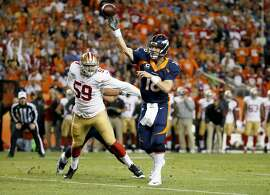 Denver Broncos quarterback Peyton Manning (18) throws his first touchdown of the game as San Francisco 49ers linebacker Aaron Lynch (59) defends during the first half of an NFL football game Sunday, Oct. 19, 2014, in Denver. (AP Photo/Jack Dempsey)