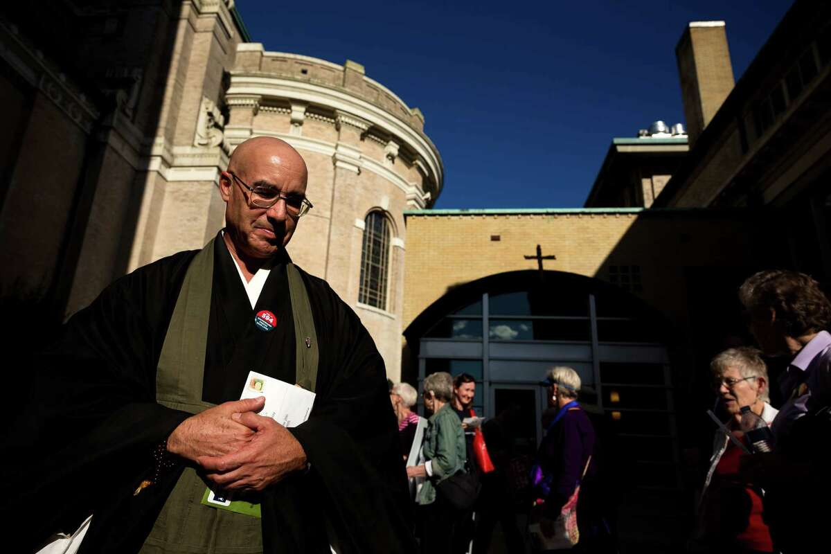 Genjo Marinello, left, of Seattle Zen Temple, clutches his completed ballot during a march against gun violence in support of the Seattle faith community's I-594 campaign Sunday, October 19, 2014, in Seattle, Washington. The initiative makes sure anyone buying a gun in Washington State passes the same background check, no matter where they buy the gun and no matter whom they buy it from.