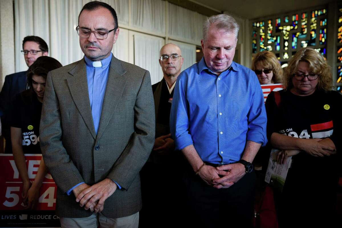 Rev. Sandy Brown, left, and Seattle Mayor Ed Murray, right, bow their heads in prayer before a march against gun violence in support of the Seattle faith community's I-594 campaign Sunday, October 19, 2014, in Seattle, Washington. The initiative makes sure anyone buying a gun in Washington State passes the same background check, no matter where they buy the gun and no matter whom they buy it from.