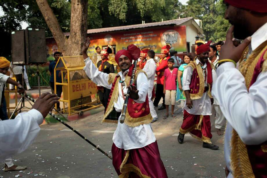 Indian folk artists dance as BJP supporters celebrate outside the BJP office in New Delhi. Photo: Tsering Topgyal, STR / AP