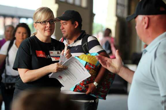 Christine Wade, a registered nurse at the University of Texas Medical Branch, greets Carnival Magic passengers disembarking in Galveston with Ebola fact sheets and a bottle of hand sanitizer.