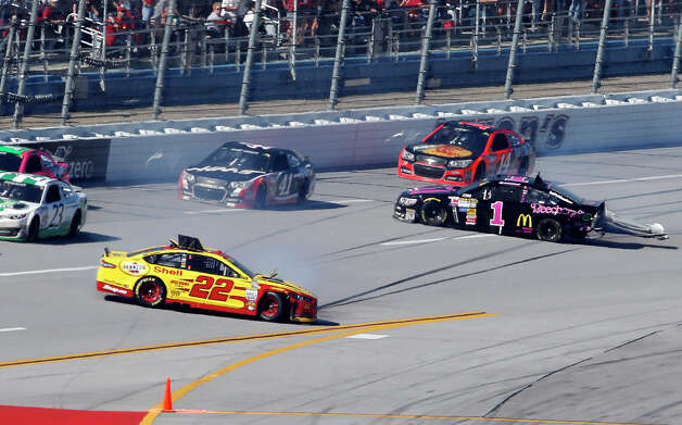 Joey Logano (22) and Jamie McMurray (1) crash as Kurt Busch (41) and Tony Stewart (14) pass by during the NASCAR Sprint Cup Series auto race at Talladega Superspeedway, Sunday, Oct. 19, 2014, in Talladega, Ala. (AP Photo/Butch Dill) ORG XMIT: ALJB117 Photo: Butch Dill / FR155191 AP