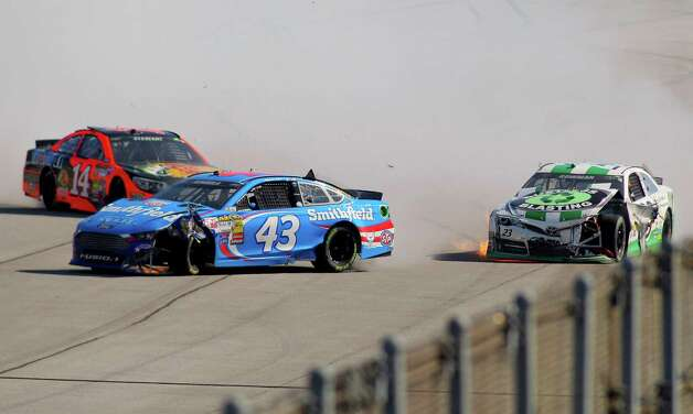 Alex Bowman, right, wrecks with Tony Stewart (14) and Aric Almirola (43) during the NASCAR Sprint Cup Series auto race at Talladega Superspeedway, Sunday, Oct. 19, 2014, in Talladega, Ala. (AP Photo/Greg McWilliams) ORG XMIT: ALJB118 Photo: Greg McWilliams / FR150231 AP