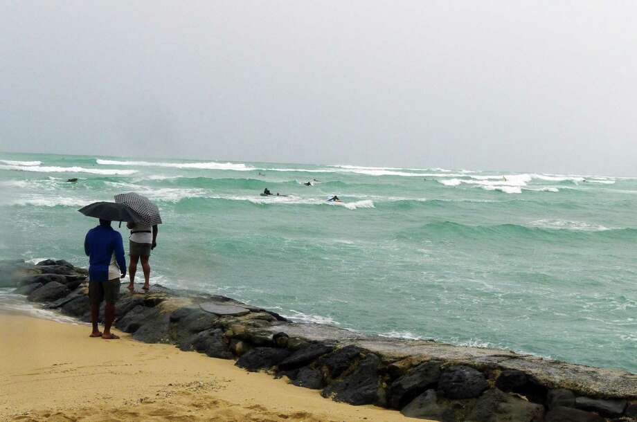Tourists watched surfers in choppy waves at Waikiki Beach  this weekend as Hurricane Ana largely bypassed Honolulu. Photo: Cathy Bussewitz / Associated Press / AP