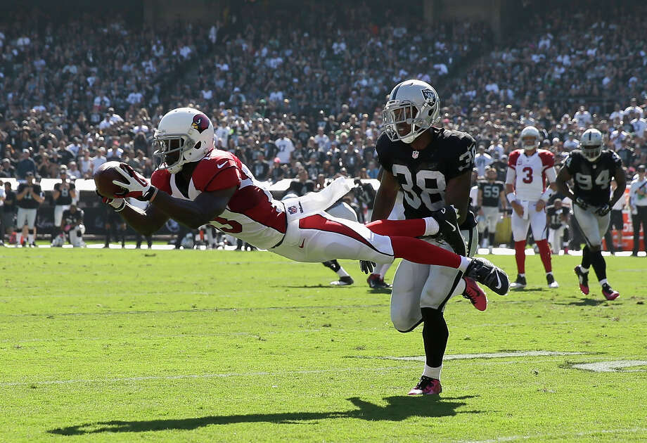 Oakland's T.J. Carrie (38) can only watch as Arizona's Jaron Brown defies gravity to make a diving catch in the first half of the Cardinals' 24-13 victory Sunday. Photo: Ezra Shaw, Staff / 2014 Getty Images