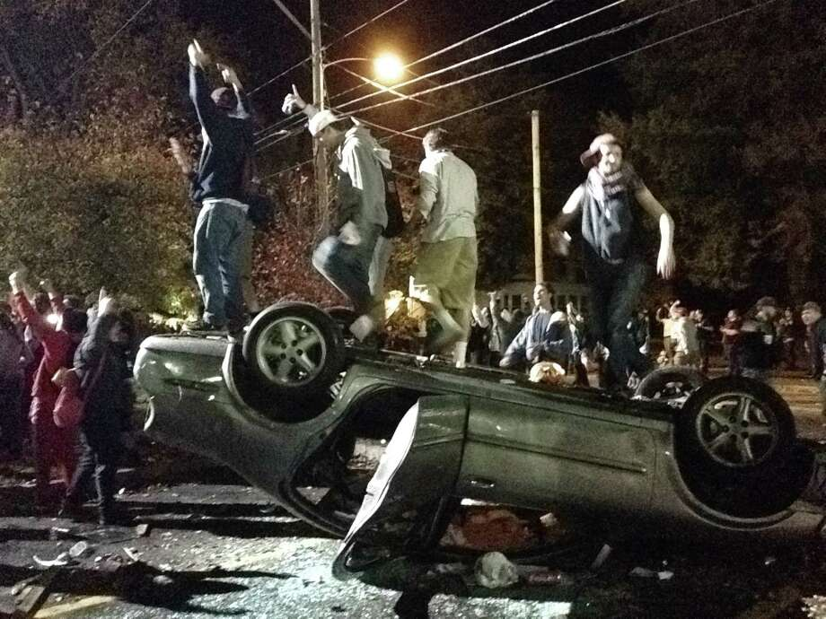 People stand atop an overturned car in Keene, N.H. on Saturday, Oct. 18, 2014, during a night of violent parties that led to destruction, dozens of arrests and multiple injuries, near the city's annual pumpkin festival.  The parties around the school coincided with the annual Keene Pumpkin Festival, where the community tries to set a world record of the largest number of carved and lighted jack-o-lanterns in one place. (AP Photo/The Boston Globe, Jeremy Fox)  BOSTON HERALD OUT, QUINCY OUT; NO SALES ORG XMIT: MABOD201 Photo: Jeremy Fox / The Boston Globe