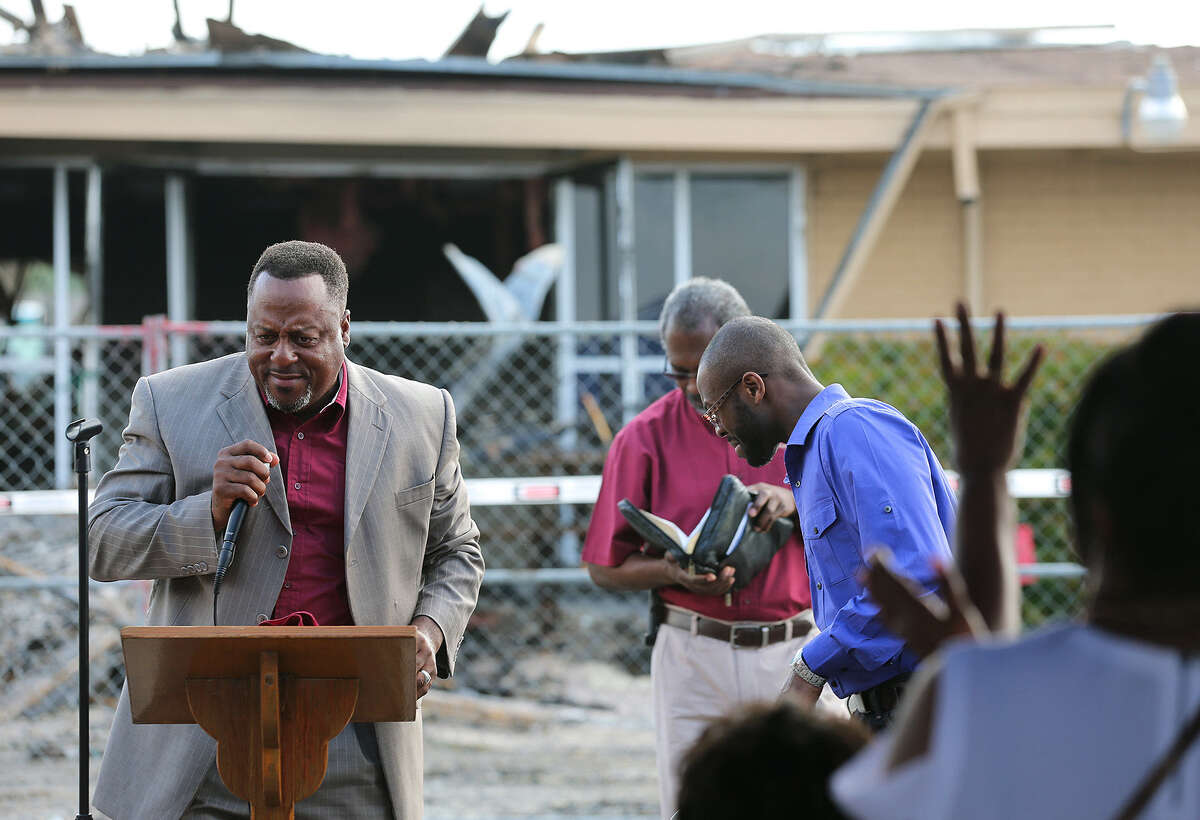 The Rev. Jeffrey Garner preaches during Sunday's Service of Healing at New Jerusalem Baptist Church. The service was held in the parking lot a week after a fire destroyed the church.