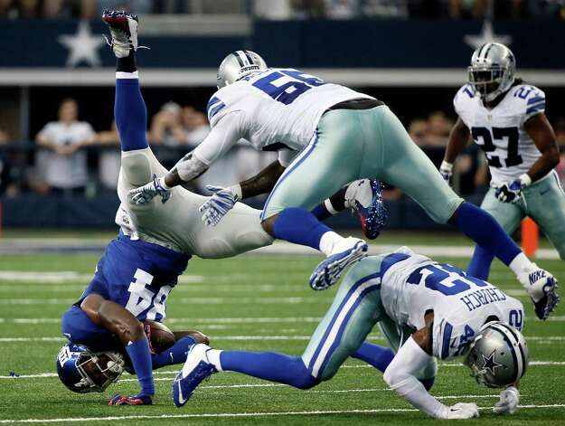 New York Giants tight end Larry Donnell (84) is upended after catching a pass by Dallas Cowboys middle linebacker Rolando McClain (55) and free safety Barry Church (42) during the first half of an NFL football game Sunday, Oct. 19, 2014, in Arlington, Texas. (AP Photo/Brandon Wade) ORG XMIT: CBS168 Photo: Brandon Wade / FR168019 AP