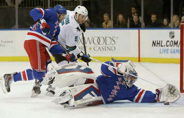 New York Rangers goalie Henrik Lundqvist (30), of Sweden, makes a save with San Jose Sharks defenseman Jason Demers (5) challenging and New York Rangers left wing Rick Nash defending during the first period of an NHL hockey game at Madison Square Garden in New York, Sunday, Oct. 19, 2014. (AP Photo/Kathy Willens) ORG XMIT: NYKW101 Photo: Kathy Willens / AP