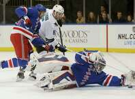 New York Rangers goalie Henrik Lundqvist (30), of Sweden, makes a save with San Jose Sharks defenseman Jason Demers (5) challenging and New York Rangers left wing Rick Nash defending during the first period of an NHL hockey game at Madison Square Garden in New York, Sunday, Oct. 19, 2014. (AP Photo/Kathy Willens) ORG XMIT: NYKW101