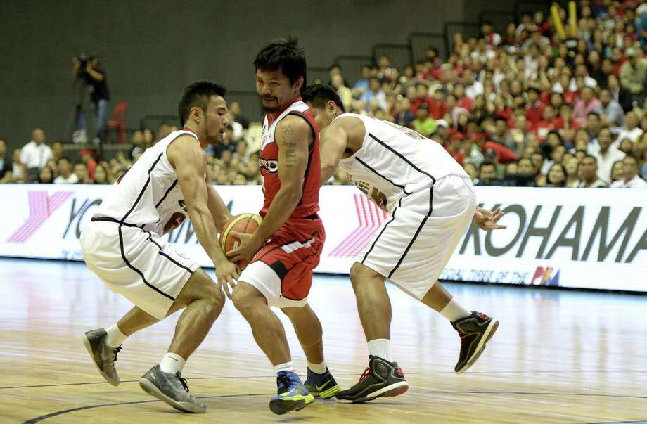 Boxing champion Manny Pacquiao, center, stands tall in the ring, but he was a bit undersized when making his pro basketball debut Sunday in the Philippines. Photo: NOEL CELIS, Stringer / AFP