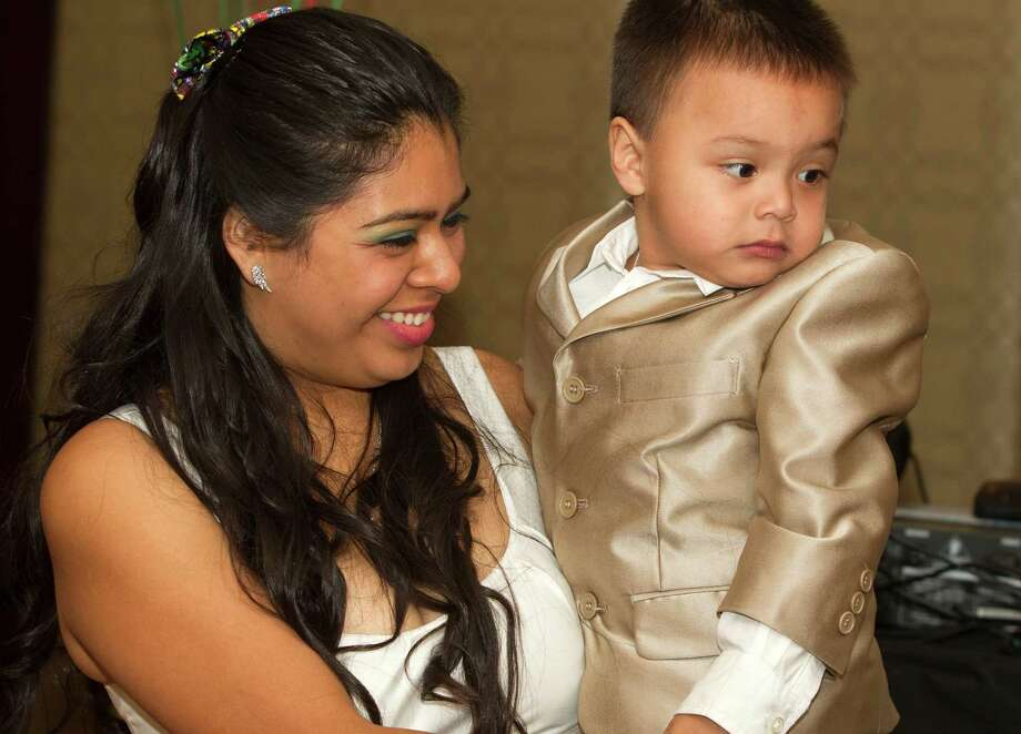 Elys Espinoza is all smiles as she holds her son, Caleb, during his third birthday party at the Four Seasons hotel on Sunday.  The little boy is in remission from liver cancer.  Photo: J. Patric Schneider, Freelance / © 2014 Houston Chronicle