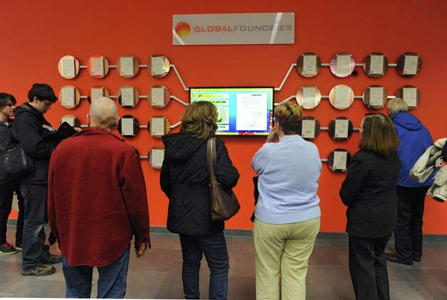 Visitors look at patented wafers on a display at the GlobalFoundries Fab 8 campus during an open house event on Monday, Nov. 11, 2013 in Malta, N.Y. (Lori Van Buren / Times Union) Photo: Lori Van Buren / 00024537A