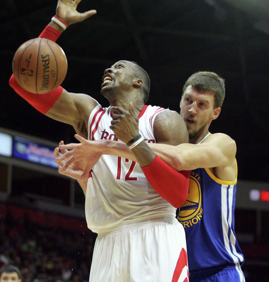 Dwight Howard gets back in the swing of things Sunday, getting wrapped up from behind by the Warriors' David Lee, right. Photo: Delcia Lopez, FRE / FR18466 AP