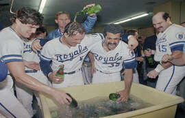 The Royals' 1985 title was epic and electrified a city. Above left, Redwood High School's Buddy Biancalana slides into home plate; Above right, George Brett is at the center of the champagne celebration, no goggles necessary.