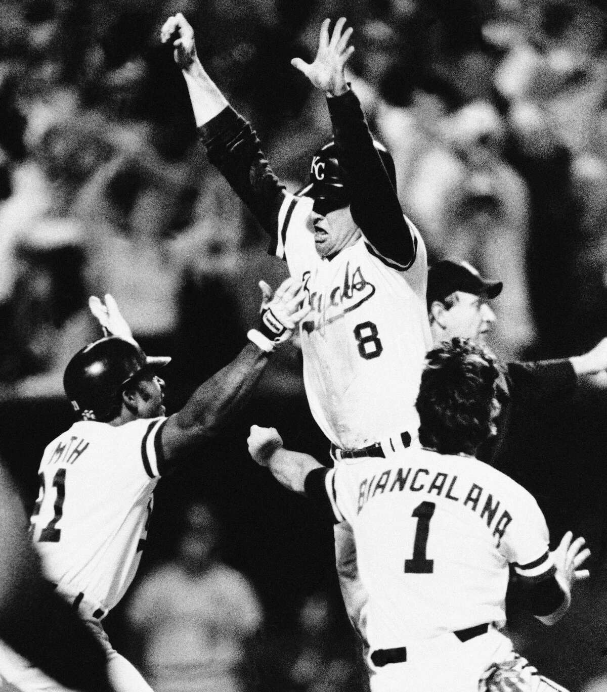 Kansas City Royals Jim Sundberg (8) leaps into the arms of teammates Lonnie Smith, left, and Buddy Biancalana after Sundberg scored in the ninth inning to beat the St. Louis Cardinals, 2-1, in a World Series game, Saturday, Oct. 26, 1985, Kansas City, Mo. (AP Photo/Rusty Kennedy)
