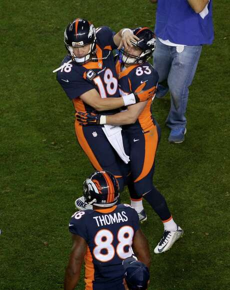 Peyton Manning is joined by Wes Welker (83), who caught his second touchdown pass Sunday night, and Demaryius Thomas, who was on the receiving end of touchdowns three and four, in celebrating the record-breaker. Photo: David Zalubowski, STF / AP