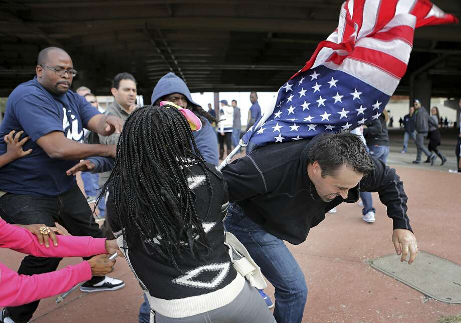 Protesters fight to regain control of a flag that was taken by a fan, right, leaving the Edward Jones Dome after an NFL football game between the St. Louis Rams and the Seattle Seahawks in St. Louis on Sunday, Oct. 19, 2014. Police say two women have been arrested after dozens of Rams fans and Ferguson protesters clashed. The scuffle broke out when fans argued with the protesters who had been yelling and chanting about the killing of Michael Brown, a black 18-year-old, by a white police officer. (AP Photo/St. Louis Post-Dispatch, David Carson) Photo: David Carson, Associated Press