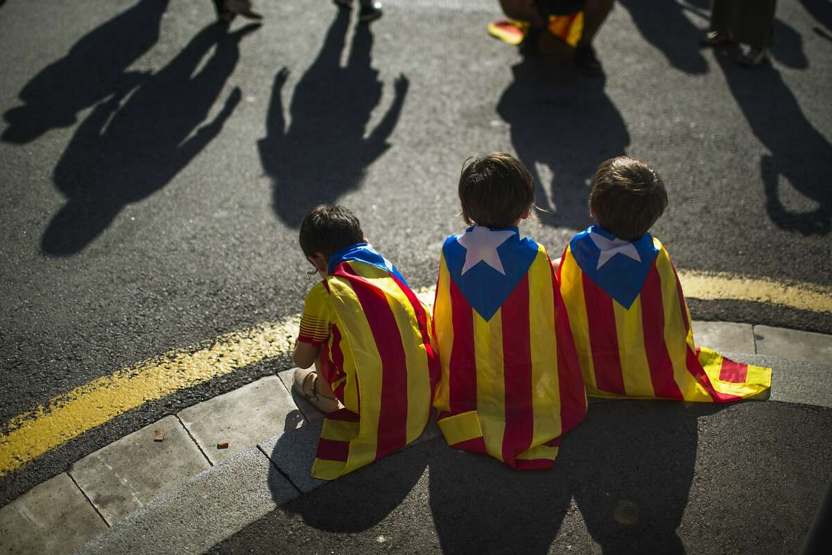 Boys wearing estelada or pro independence flags sit during a rally in Catalonia square in Barcelona, Spain, Sunday, Oct. 19, 2014. Thousands of demonstrators crowded a central square in Barcelona during the main campaign event organized by two major pro independence civil society organizations ahead of the vote scheduled for Nov. 9th. Spain's wealthy Catalonia region calls off an independence vote but says an unofficial poll would still be held next month to gauge secessionist sentiment. Separatists in northeastern Catalonia, which has 7.5 million people, have been trying for several years to hold a breakaway vote from Spain to carve out a new Mediterranean nation. (AP Photo/Emilio Morenatti)
