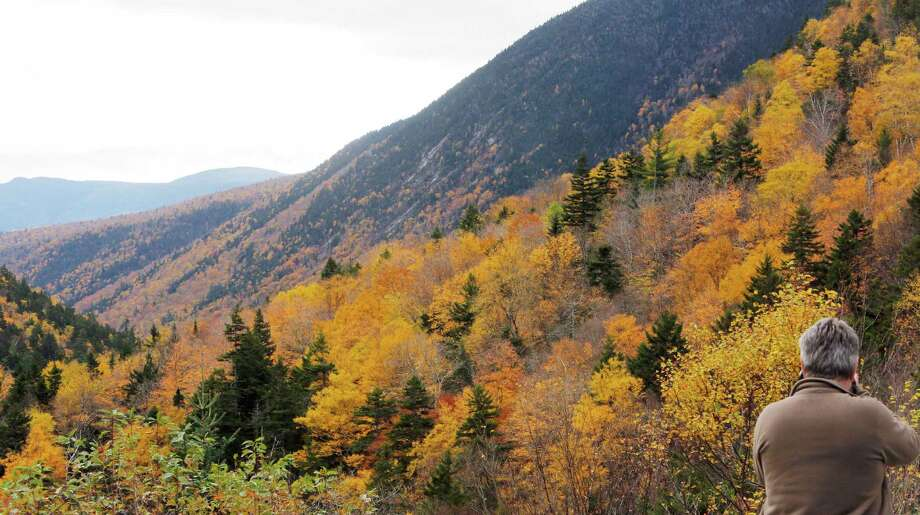 In this Monday, Oct. 13, 2014 photo, a tourist photographs Crawford Notch in Carroll, N.H., as foliage reaches peak in New Hampshire's White Mountains. Officials say tourists will spend upwards of $1 billion to catch a glimpse of the red, yellow and orange hues on the trees, and the windfall is steadily rising as the economy regains strength. (AP Photo/Jim Cole) ORG XMIT: CON202 Photo: Jim Cole / AP