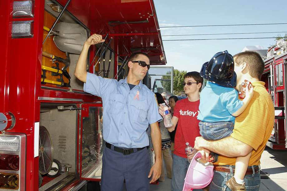 Fireman Robert Lyng shows a visiting family the features of a fire truck at the new West I-10 Fire Station No. 3 located at Westgreen and Highland Knolls during its open house on Oct. 19. Photo: Diana L. Porter, For The Chronicle / © Diana L. Porter