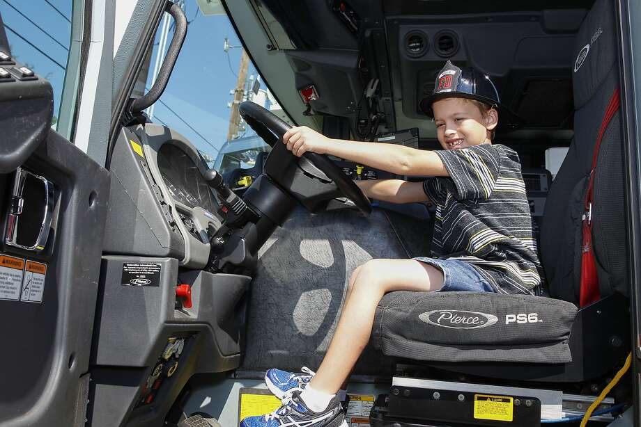 Ky Blake, age 7, takes the wheel of a fire truck at the new West I-10 Fire Station Number 3 located at Westgreen and Highland Knolls during its open house to the public on October 19, 2014. Photo: Diana L. Porter, For The Chronicle / © Diana L. Porter