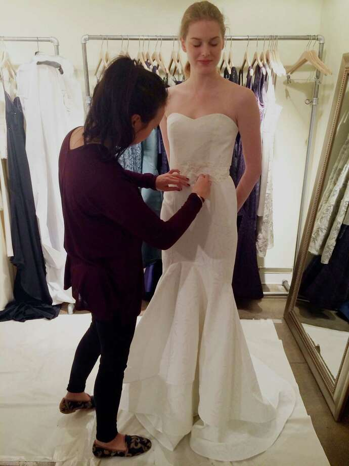 Greenwich designer Katie Fong works on one of her custom dresses. Fong is launching a new line of graduation gowns later this week. Photo: Contributed Photo / Greenwich Time Contributed