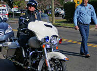 Officer James Chueka takes delivery of a new Harley-Davidson motorcycle from Ted Sjurseth, founder and president of America's 911 Foundation.