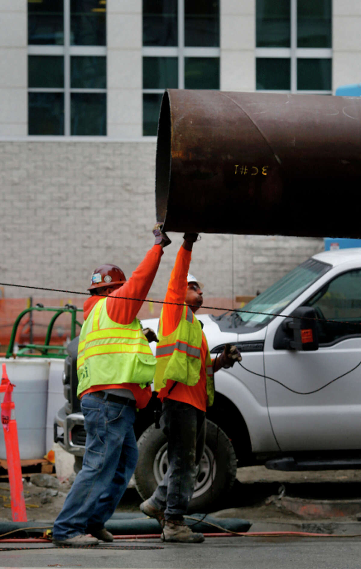 A construction crew maneuvers large steel pipes into place to be used for internal bracing.