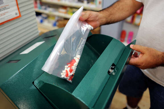 Marwan Nasrah puts unused pills into a drug disposal box at Daniel's Pharmacy in S.F.