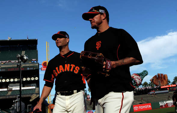 Giants starting pitchers Tim Hudson (left) and Jake Peavy walk off the field before playing the Washington Nationals in Game 4 of National League Divisional Series at AT&T Park in San Francisco on Oct. 7.