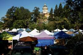 The tents of the Foothill Farmers Market are seen with the historic Auburn Courthouse in the background.