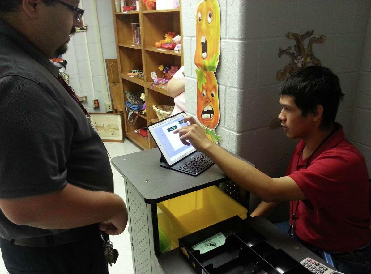 ETC student Ivan Ramón (right) works as a cashier for the Helper's Hand thrift store as teacher Roberto De Leon looks on.