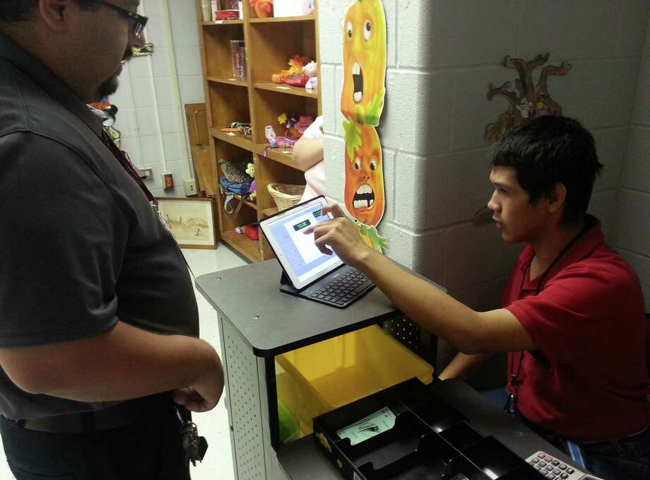 ETC student Ivan Ramón (right) works as a cashier for the Helper's Hand thrift store as teacher Roberto De Leon looks on. Photo: Jeremy Gerlach / San Antonio Express-News