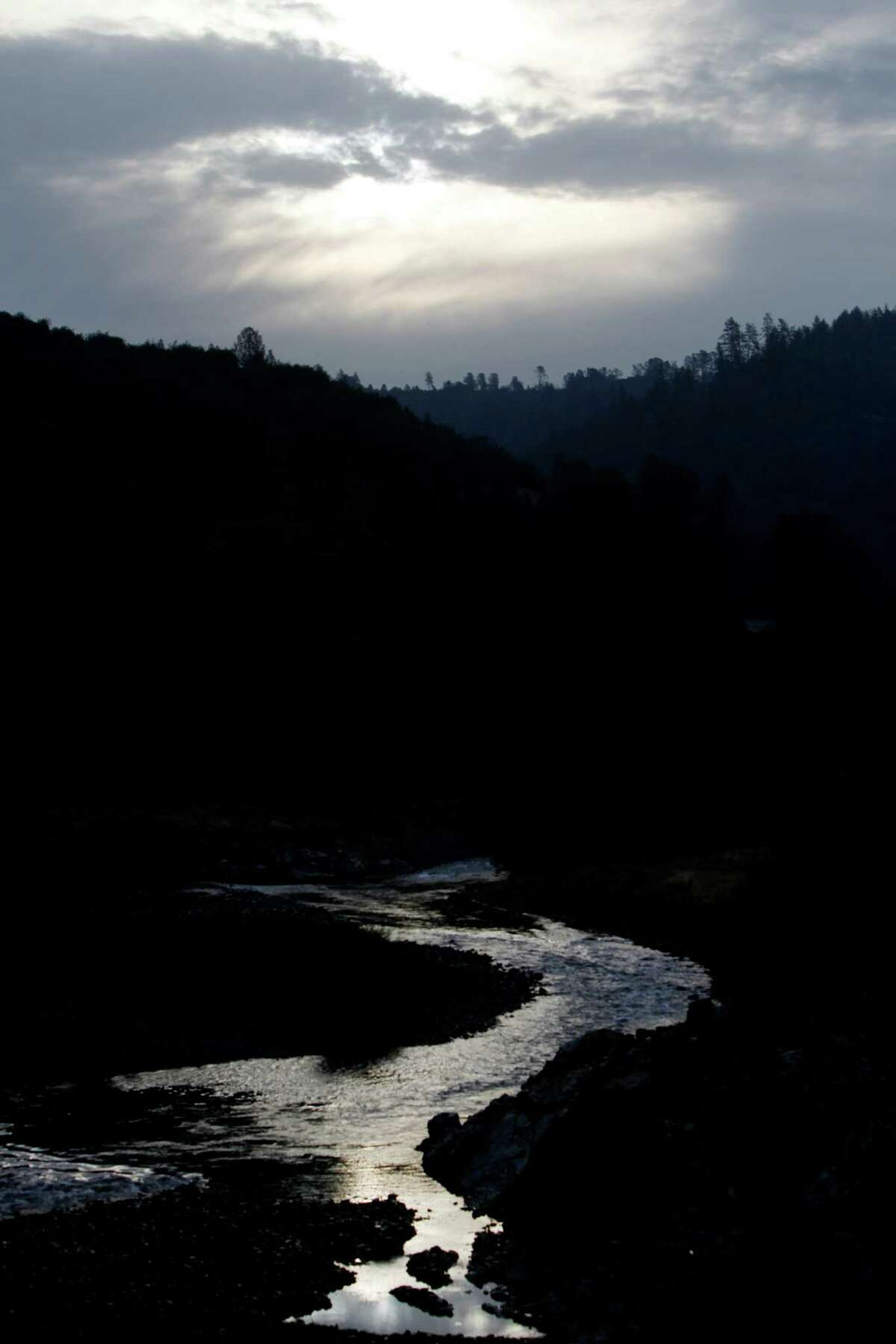 The sun rises through clouds above the American River near the Foresthill Bridge in Auburn.
