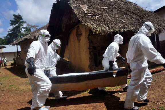 """Health workers carry the body of a woman suspected of contracting the Ebola virus in Bomi county situated on the outskirts of Monrovia, Liberia, Monday, Oct. 20, 2014.  Liberian President Ellen Johnson Sirleaf said Ebola has killed more than 2,000 people in her country and has brought it to """"a standstill,"""" noting that Liberia and two other badly hit countries were already weakened by years of war. (AP Photo/Abbas Dulleh)"""
