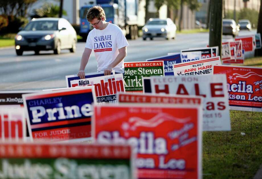Evan Lee, campaign manager for Sarah Davis, places yard signs at the Metropolitan Multi Service Center on West Gray on Monday. Photo: Gary Coronado, Staff / © 2014 Houston Chronicle