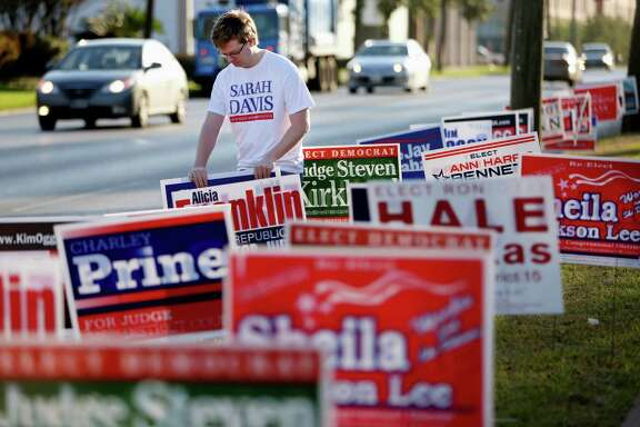 Evan Lee, campaign manager for Sarah Davis, places yard signs at the Metropolitan Multi Service Center on West Gray on Monday.